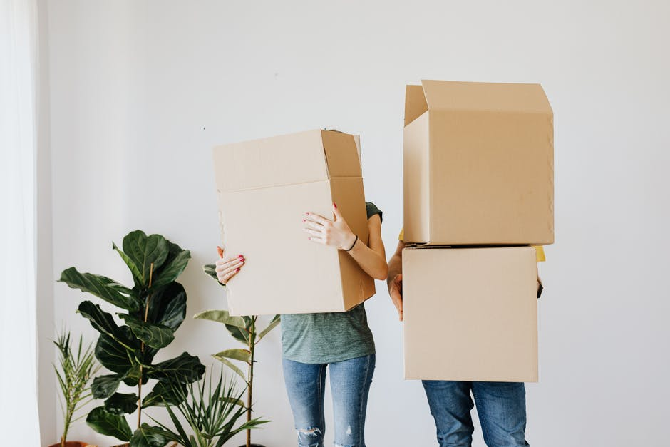 A two person holding cardboard boxes